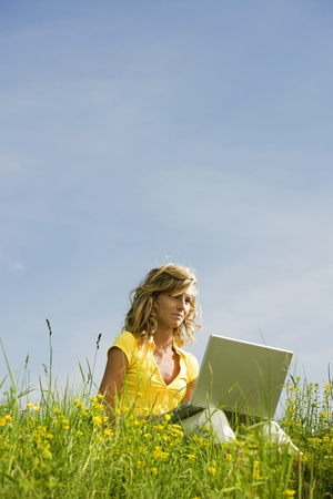 Beautiful woman sitting on the grass with her laptop photo