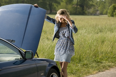 Worried young woman with her broken car photo