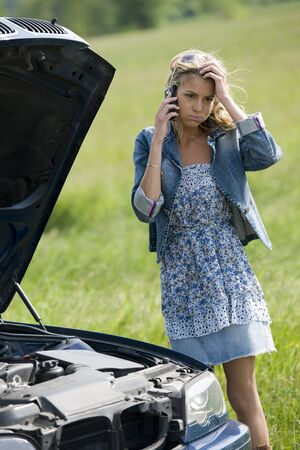 Worried young woman with her broken car, calling for assistance photo