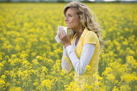 Giovane donna starnuti in un prato di fiori. Concetto: allergia stagionale.