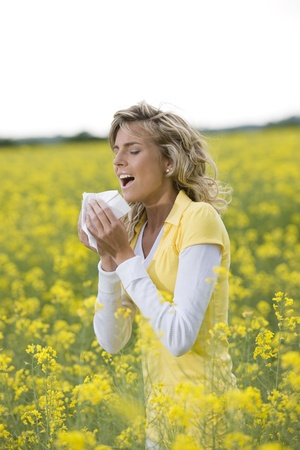 Young woman sneezing in a flowers meadow. Concept: seasonal allergy. photo