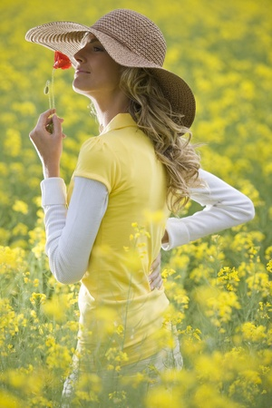 Beautiful woman holding a poppy flower in a field photo