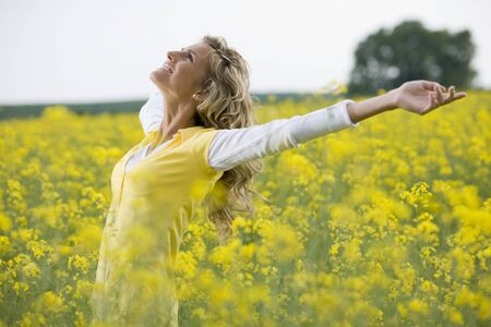 Beautiful woman in a yellow flowers field with arms outstretched Stock Photo - 9864923