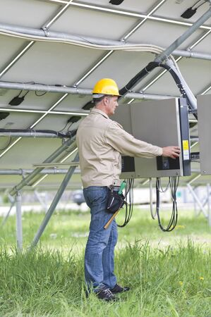 Technicians Working Under Solar Panels photo