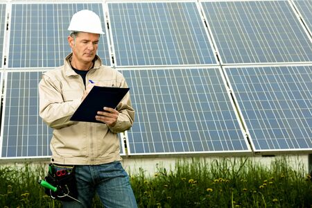 Technician making inspection at solar power station Stock Photo