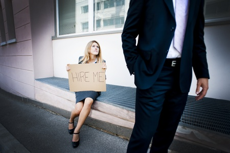 begging: Young woman asking for a job, man looking indifferent Stock Photo