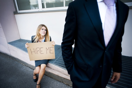 looking for a job: Young woman asking for a job, man looking indifferent Stock Photo