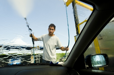 Young man wasing a car using compression water photo