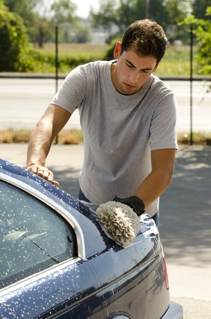 bubble car: Young man cleaning a car with sponge