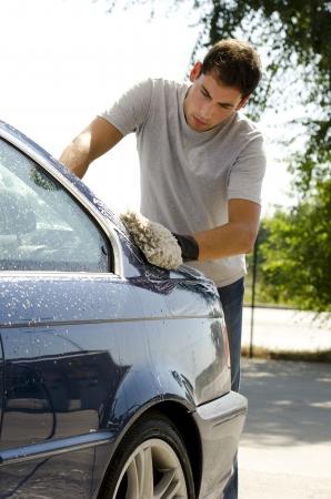 cleaning car: Joven limpiar un coche con una esponja