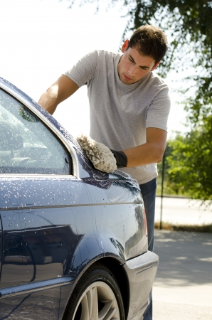 domestic car: Young man cleaning a car with sponge