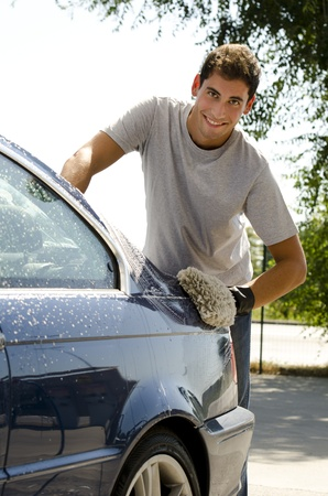 dirty car: Young man cleaning a car with sponge