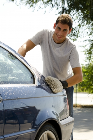 Young man cleaning a car with sponge