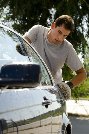 washing car: Young man cleaning a car with sponge