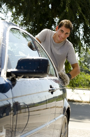 Young man cleaning a car with sponge photo