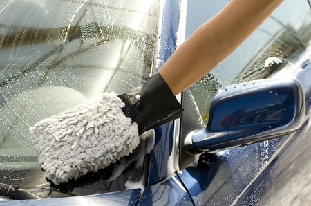 Close-up van een man schoonmaken van een auto met spons