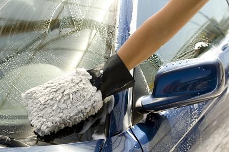 Close-up von einem Mann Reinigung ein Auto mit Schwamm