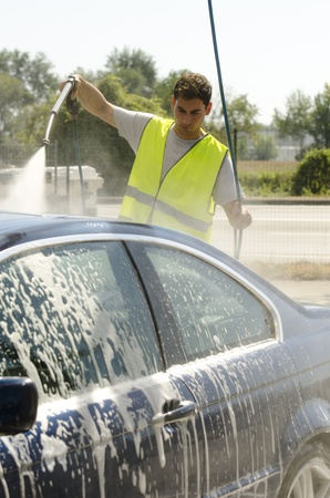 Young man working at car wash station photo