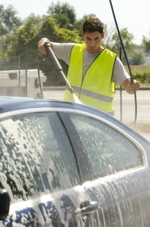 dirty car: Young man working at car wash station