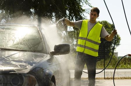 cleaning car: Hombre joven que trabaja en la estaci�n de lavado de coches Foto de archivo