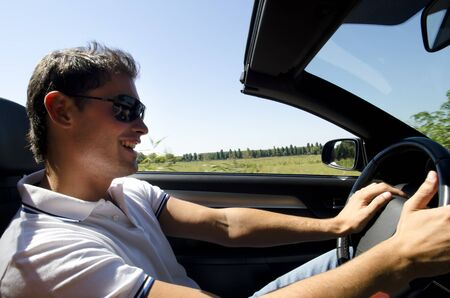 getting away from it all: Happy young man driving a convertible car