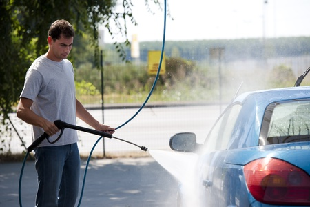 Young man washing his car with compression water photo
