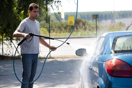 Young man washing his car with compression water Standard-Bild
