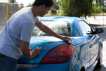 Young man washing his car with sponge photo