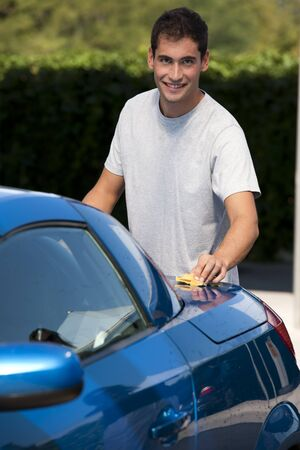 domestic car: Happy young man cleaning his car with sponge