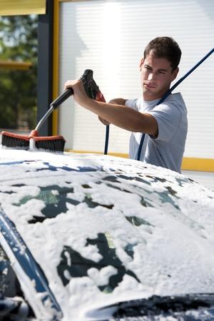 autolavaggio: Giovane uomo lavare la macchina con l'acqua di compressione