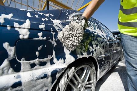 Close-up van een man schoonmaken van zijn auto met een spons