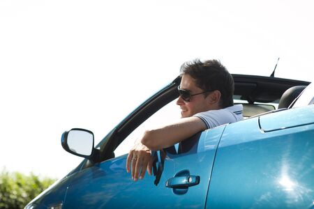 Side view of a man driving his convertible car photo