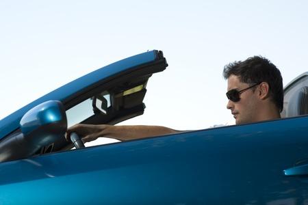 convertible car: Low angle view of a man driving his convertible car