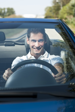 Front view of a young man driving his convertible car Stock Photo