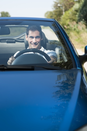 Front view of a young man driving his convertible car photo
