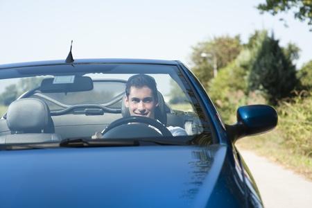 Vooraanzicht van een jonge man rijdt zijn cabrio auto