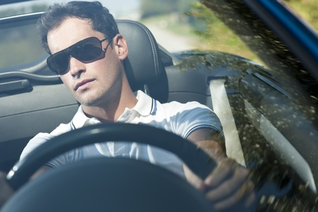cabrio: Vooraanzicht van een jonge man rijdt zijn cabrio auto