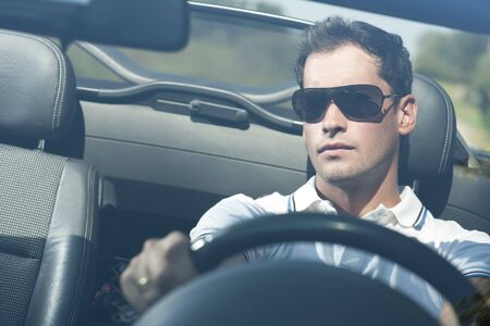 Front view of a young man driving his convertible car Foto de archivo