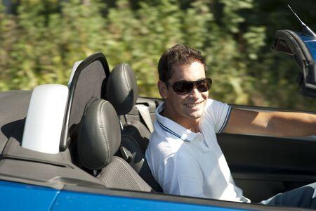 Young man driving his convertible car Stock Photo - 13036972