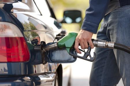 Service station werknemer tanken auto met brandstof, close-up