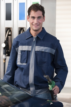 Service station worker filling up car with fuel
