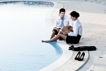 Two young people working free with feet in the pool photo