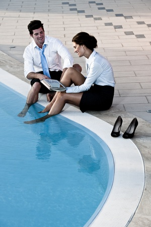neckties: Two young people working free with feet in the pool