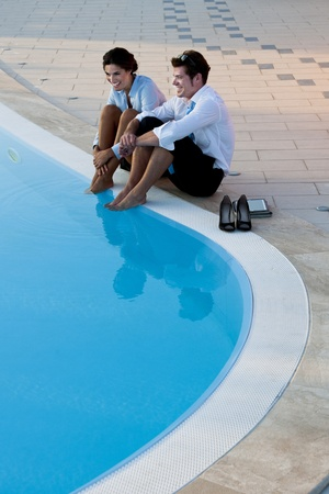 Young couple or businsspeople relaxing by pool photo