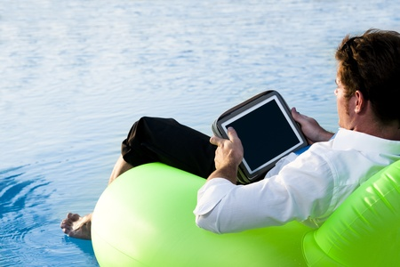 Relaxed man working with tablet PC on pool photo