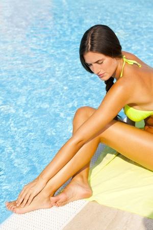 blue bikini: Beautiful young woman sitting by swimming-pool