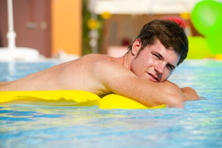Young man relaxing on swimming-pool Stock Photo - 13245057