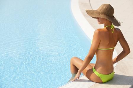 Mooie jonge vrouw zat bij zwembad, veel kopie-ruimte