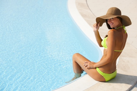 Beautiful young woman sitting by swimming-pool, lots of copy-space Stock Photo - 13245047