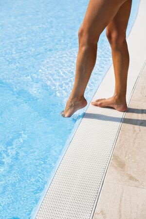 Young woman entering swimming-pool photo